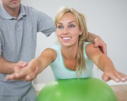 Physiotherapist correcting patient doing exercise on exercise ball - pelvic foor rehabilitation